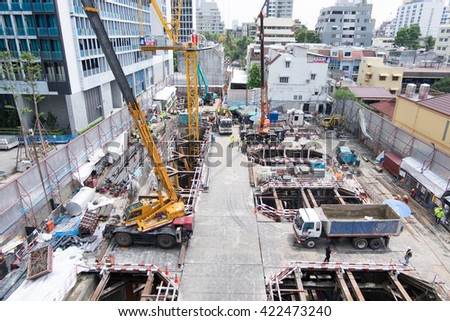 BANGKOK- MAY 18, 2016: Yellow excavator on a construction and Tower,Bangkok, Thailand - stock photo
