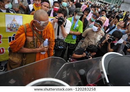 BANGKOK - NOV 24: A Buddhist monk confronts riot police while attending a nationalist anti-government rally organised by the Pitak Siam group on Nov 24, 2012 in Bangkok, Thailand. - stock photo