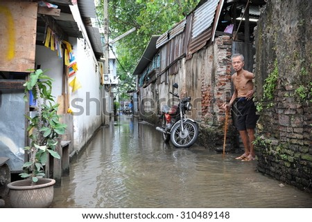 BANGKOK - NOV 22: A man looks out on a flooded alley in Chinatown on Nov 22, 2011 in Bangkok, Thailand. The Thai capital is experiencing its worst flooding in decades with much of the city inundated. - stock photo