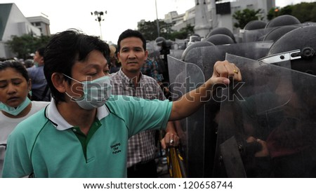 BANGKOK - NOV 24: A masked protester from the nationalist Pitak Siam confronts riot police during a violent anti-government rally on Nov 24, 2012 in Bangkok, Thailand. - stock photo
