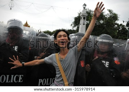 BANGKOK - NOV 24: A protester confronts riot police during a violent city centre anti government rally on Nov 24, 2012 in Bangkok, Thailand. Protesters call for a coup to overthrow the government. - stock photo