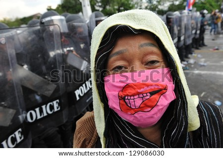 BANGKOK - NOV 24: A protester from the nationalist Pitak Siam confronts riot police during a violent anti-government rally on Nov 24, 2012 in Bangkok, Thailand. - stock photo