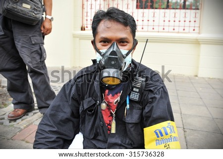 BANGKOK - NOV 24: A protester wearing a gas mask attends a violent anti-government rally organised by the nationalist Pitak Siam group on Nov 24, 2012 in Bangkok, Thailand. - stock photo