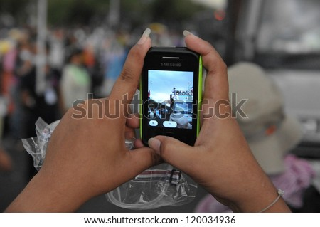 BANGKOK - NOV 24: A protesters uses a smartphone to video an anti-government Pitak Siam rally at Makhawan Bridge on Nov 24, 2012 in Bangkok, Thailand.