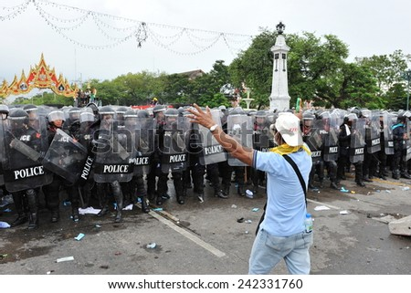 BANGKOK - NOV 24: An anti government protester confronts riot police during a violent rally on Nov 24, 2012 in Bangkok, Thailand. The protesters call for the government to be overthrown. - stock photo