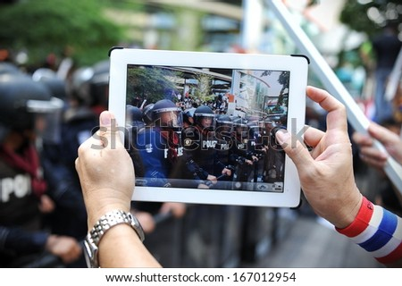 BANGKOK - NOV 29: An anti-government protesters uses a tablet device to capture a police line at a large rally outside the ruling Pheu Thai party's headquarters on Nov 29, 2013 in Bangkok, Thailand. - stock photo