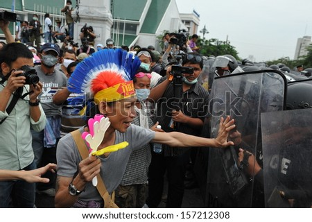 BANGKOK - NOV 24: An unidentified protester confronts riot police while participating in an anti-government rally organised by the nationalist Pitak Siam group on Nov 24, 2012 in Bangkok, Thailand. - stock photo