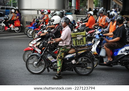 BANGKOK - NOV 14: Motorcyclists wait at a junction during rush hour on Nov 14, 2012 in Bangkok, Thailand. Motorcycles are often the transport of choice for Bangkok's heavily congested roads.  - stock photo