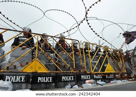 BANGKOK - NOV 24: Riot police stand guard behind razor wire during a violent anti government rally in the Thai capital on Nov 24, 2012 in Bangkok, Thailand. - stock photo