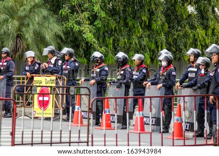BANGKOK - NOV 13: Riot police stand guard near parliament during anti-government rally on Nov 13, 2013 in Bangkok, Thailand. Protests surrounding an amnesty bill  - stock photo