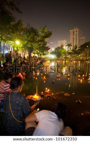 BANGKOK - NOVEMBER 21, 2010: Thai people launch candle lighted krathongs at downtown Lumpini park during the annual Thai holiday festival of Loi Krathong on November 21, 2010 in Bangkok - stock photo