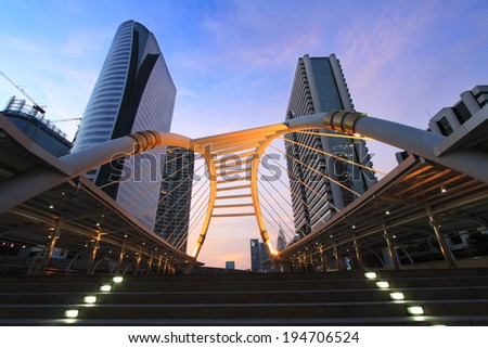 BANGKOK -OCT 02: Night view of Sathorn-Narathiwas Intersection with sky walk and tower buildings in Bangkok, Thailand on October 02, 2011. Sky walk is for transit between Bangkok sky train and bus. - stock photo