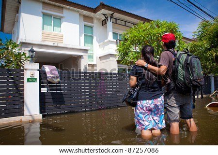 BANGKOK - OCTOBER 24: An unidentified couple looks at their flooded house on of October 24, 2011 in Bangkok, Thailand. The area is flooded due to recent monsoons. - stock photo