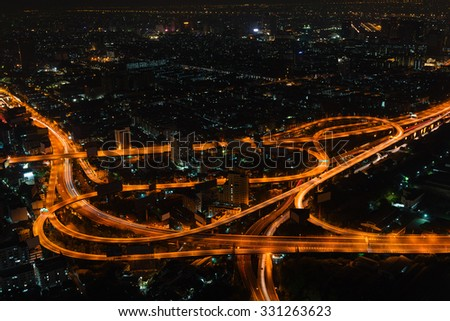 Bangkok's cityscape at night with highrise buildings and a complicated highway interchange, highlighted under the glow of sodium vapor street lamps.