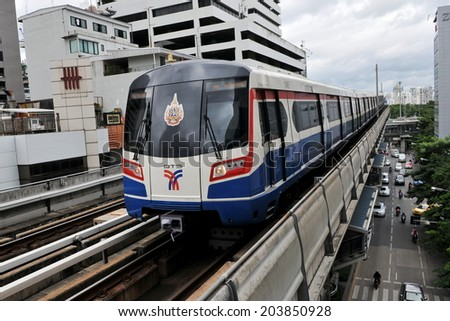 BANGKOK - SEP 12: A BTS Skytrain on speeds along elevated rails above a city centre road on Sep 12, 2011 in Bangkok, Thailand. Each train of the mass transport rail network can carry 1,000 passengers. - stock photo