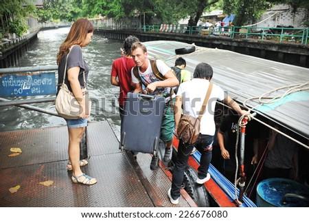 BANGKOK - SEP 15: Passengers board and disembark a boat on Klong Saen Saep canal on Sept 15, 2012 in Bangkok, Thailand. Klong Saen Saep canal runs for 18 kilometers through central Bangkok. - stock photo