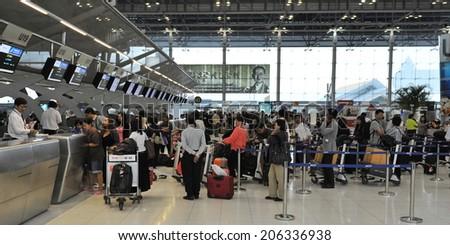 BANGKOK - SEP 19: Travellers queue at check-in counters at Suvarnabhumi Airport on Sep 19, 2012 in Bangkok, Thailand. The Thai capital's main international terminal handles 45 mln travellers annually. - stock photo