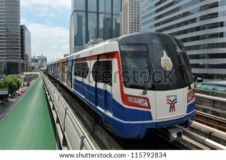 BANGKOK - SEPT 12: A BTS Skytrain on elevated rails in Sathorn district on Sept 12, 2012 in Bangkok, Thailand. Each train of the mass transport rail network can carry over 1,000 passengers. - stock photo