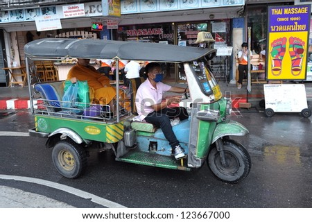 BANGKOK - SEPT 15: A tuk-tuk taxi transports a Buddhist monk along a street on Sept 15, 2012 in Bangkok, Thailand. Tuk tuks can be hired from as little as $1 or B30 a fare for shop trips. - stock photo