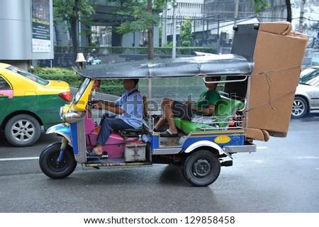 BANGKOK - SEPT 15: A tuk-tuk taxi transports a passenger along a street on Sept 15, 2012 in Bangkok, Thailand. Tuk tuks can be hired from as little as $1 or B30 a fare for shop trips. - stock photo