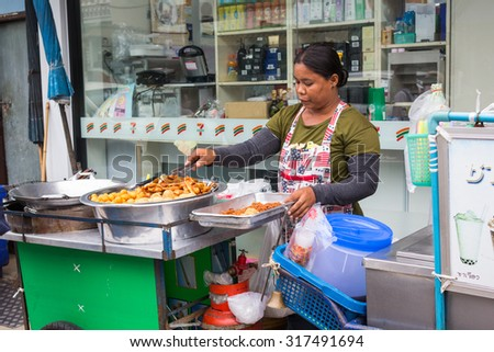 BANGKOK - 14 SEPTEMBER, 2015: women sell Thai fried banana, street food stall in front of school