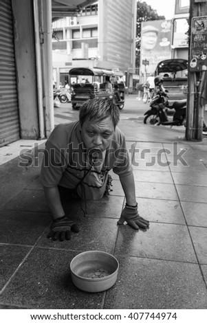BANGKOK THAILAND-Apr. 17:Beggar man crawls begging for money in Bankok,Thailand. - stock photo