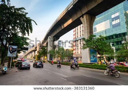 BANGKOK, THAILAND - 09 APR 2013: City street light traffic with sky train bridge overpass overhead - stock photo