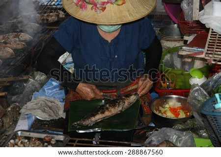 BANGKOK, THAILAND - APRIL 12: A closeup of a local Thai lady cooking in a boat on the waterway at the Taling Chan Floating Markets in Bangkok, Thailand on the 12th April, 2015.