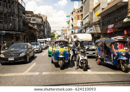 BANGKOK, THAILAND April 20, 2017: Cars, Automobile taxi with motorcycle, Tuktuk public transport on traffic road