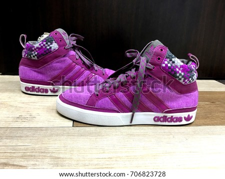 BANGKOK, THAILAND - April 17, 2016: Purple Adidas sneakers for running, football, training, showing the Adidas logo and famous three stripes.