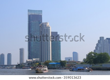 BANGKOK THAILAND - APRIL 20, 2015: Skyscraper along Chao Phraya River. Chao Phraya river  is a major river in Thailand, with its low alluvial plain forming the centre of the country.