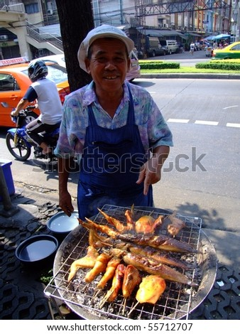 BANGKOK, THAILAND - APRIL 3: Thai man cooks and sells grilled chicken and fish on April 3, 2007 in Bangkok.