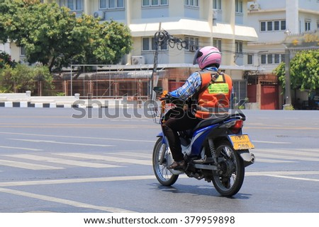 BANGKOK THAILAND - APRIL 21, 2015: Unidentified Motorbike taxi driver waits for traffic light. Motorbike taxi is one of the major public transport system in Bangkok and popular among locals.  - stock photo