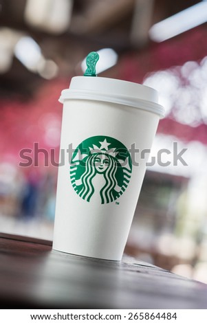 BANGKOK, THAILAND - APRIL 02, 2015: White paper cup with Starbucks logo. Starbucks is the world's largest coffee house with over 20,000 stores in 61 countries. - stock photo