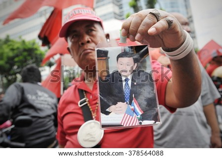 BANGKOK, THAILAND - AUG 9, 2012: A Red Shirt protester holds a portrait of former Prime Minister Thaksin Shinawatra during a rally outside the Thai Criminal Court. - stock photo