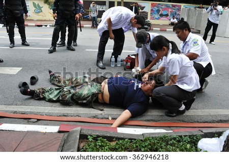 BANGKOK, THAILAND - AUG 7, 2013: An injured protester is treated by paramedics after collapsing during clashes at an anti government rally near the Thai parliament.