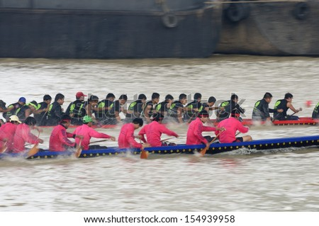 BANGKOK, THAILAND - AUG 25: Two rowing teams in full speed during Thai Long-tailed Boat Competition along Chaopraya river on August 25, 2013 at Rama 8 Bridge, Bangkok, Thailand