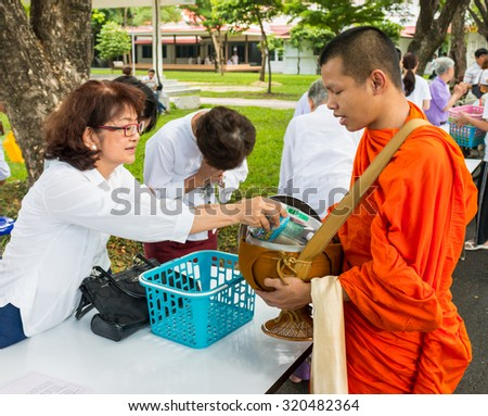 BANGKOK,THAILAND - August 15, 2015: A Lady is putting food offerings into a Buddhist monk's bowl during religious ceremony