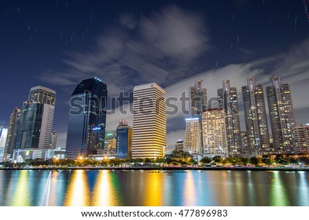 BANGKOK, THAILAND - AUGUST 27 :Cityscape view of business building from Benjakitti Park at night on August 27,2016 in Ratchadapisek, Bangkok, Thailand. With colorful light reflection the water