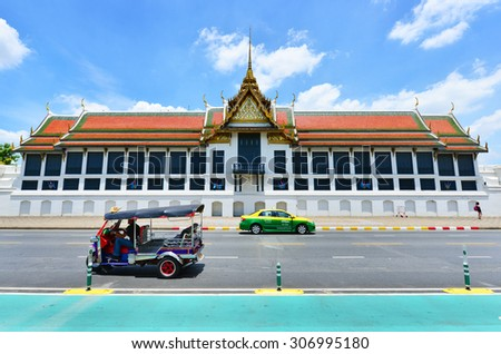 BANGKOK, THAILAND - August 14, 2015: TukTuk,Taxi on road in front of the famous Buddhist Temple Wat Phra Kaew, one of the main landmarks of Bangkok, Thailand - stock photo