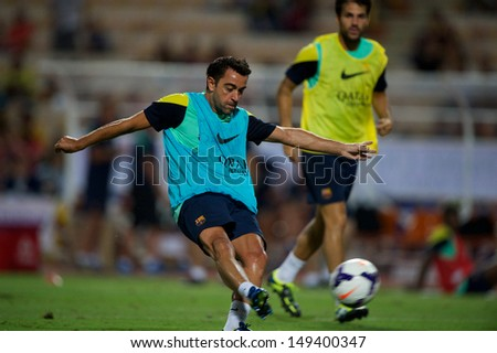 BANGKOK, THAILAND - AUGUST 06: Xavi  (L) of Barcelona FC shot the ball during Barcelona FC training session at Rajamangala Stadium on August 06, 2013 in Bangkok, Thailand.