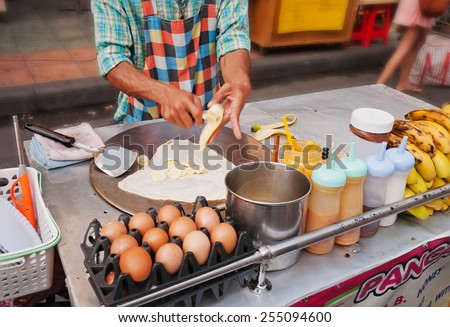 BANGKOK, THAILAND - DEC 7, 2013 : Man cooks Thai Banana Pancake on the street  Khaosan Road. Khaosan Road or Khao Sarn Road  is a short tourist walking street in central Bangkok - stock photo