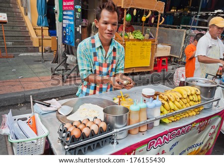 BANGKOK, THAILAND DEC 7: Man cooks Thai Banana Pancake on the street  Khaosan Road on Dec 7, 2013, in Bangkok. Khaosan Road or Khao Sarn Road  is a short tourist walking street in central Bangkok - stock photo