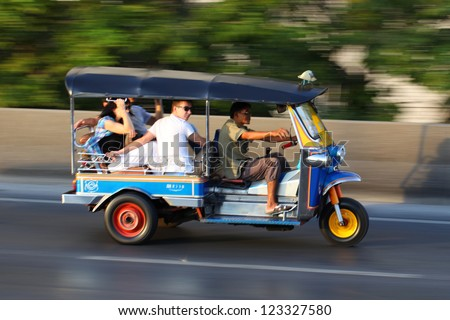 BANGKOK, THAILAND - DEC. 31 : Unidentified driver and tourists in tuk tuk along the road on December 31, 2012 in Bangkok Thailand. Tuk tuk is very good transmission for traffic jam in the city - stock photo