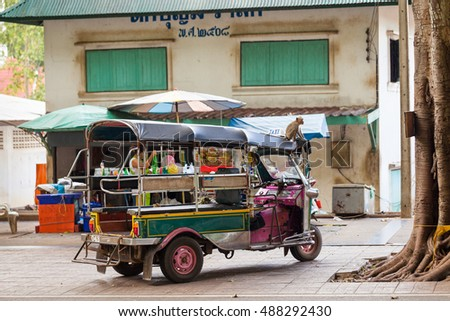 BANGKOK, THAILAND - DEC. 8, 2015 Wild baby monkey sitting on top popular Traditional asian transport taxi tuk-tuk on background old thai style house / Thailand