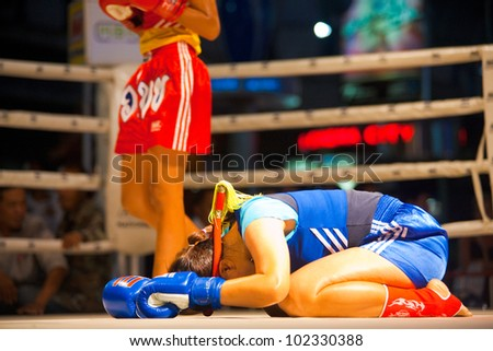 BANGKOK, THAILAND - DECEMBER 8, 2010: An unidentified female muay thai fighter bows her head on the ring to perform a kickboxing ritual called the wai khru on December 8, 2010 in Bangkok, Thailand - stock photo