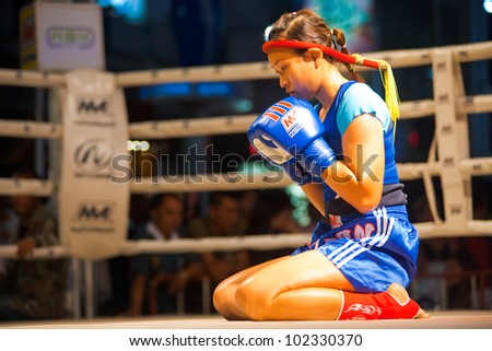 BANGKOK, THAILAND - DECEMBER 8, 2010: An unidentified female muay thai fighter reflects in a kickboxing ritual called the wai khru meant to honor her teachers on December 8, 2010 in Bangkok, Thailand - stock photo