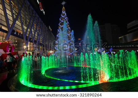 BANGKOK, THAILAND, DECEMBER 25, 2014: Colorful fountain and huge Christmas tree on the Central World square in front of the mall in Bangkok, Thailand - stock photo