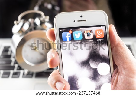 Bangkok, Thailand - December 10, 2014: Hand holding iPhone with social media applications on screen ,Social media are using for information sharing and networking. - stock photo