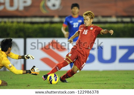 BANGKOK THAILAND-DECEMBER 13:Jakkraphan Pornsai of Thailand (red) in action during the AFF Suzuki Cup between  Malaysia and Thailand at Supachalasai stadium on Dec 13, 2012 in Bangkok,Thailand.
